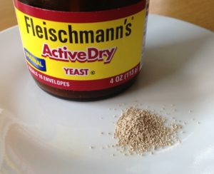 a jar of active dry yeast with a small pile of yeast granules
